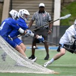 Senior Griffin Fries tries to get the ball while two Rockhurst players defend him. Photo by Julia Percy