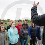 Choir director Ken Foley directs the chamber choir as they perform the national anthem at the girls varsity soccer senior night. Photo by Luke Hoffman