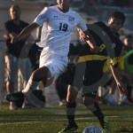 Junior Sean Brooks jumps over a West player to dribble towards the goal. Photo by Sarah Golder