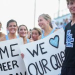 Senior Chloe Sowden and junior Avery Gray hold up signs for fellow cheerleader senior Savannah Bahr during homecoming nominee walkouts. Photo by Aislinn Menke