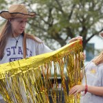 Sophomore Sydney Beck holds out the gold streamers to put them on the float and accidentally hits friend, Sadie Mcdonald, in the face. Photo by Morgan Woods