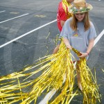 Sophomore Sadie Mcdonald trims the gold streamers on the side of the float with scissors. Photo by Morgan Woods