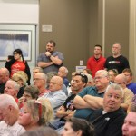 """The crowd of attendees observe Rep. Sharice Davids —some with high regard, others with """"disappointment,"""" according to an attendee commenting for this story on the condition of anonymity. Photo by Ben Henschel."""