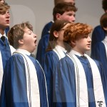 """Sophomore Henry Krause sings along to """"Her Voice"""" with the Varsity Men's Choir. Photo by Megan Stopperan"""