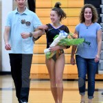 Senior Abby Gorman walks with her parents at the beginning of the meet. Photo by Kate Nixon