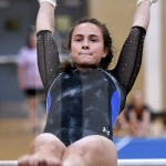 Before gaining momentum to prepare for dismount, senior Brooklyn Beck focuses on the bar. Photo by Kate Nixon
