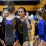 After junior Avery Wilson performed her beam routine, senior Brooklyn Beck high fives her. Photo by Kate Nixon
