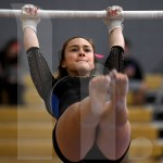 Senior Brooklyn Beck warms up on the bars before competing. Photo by Kate Nixon