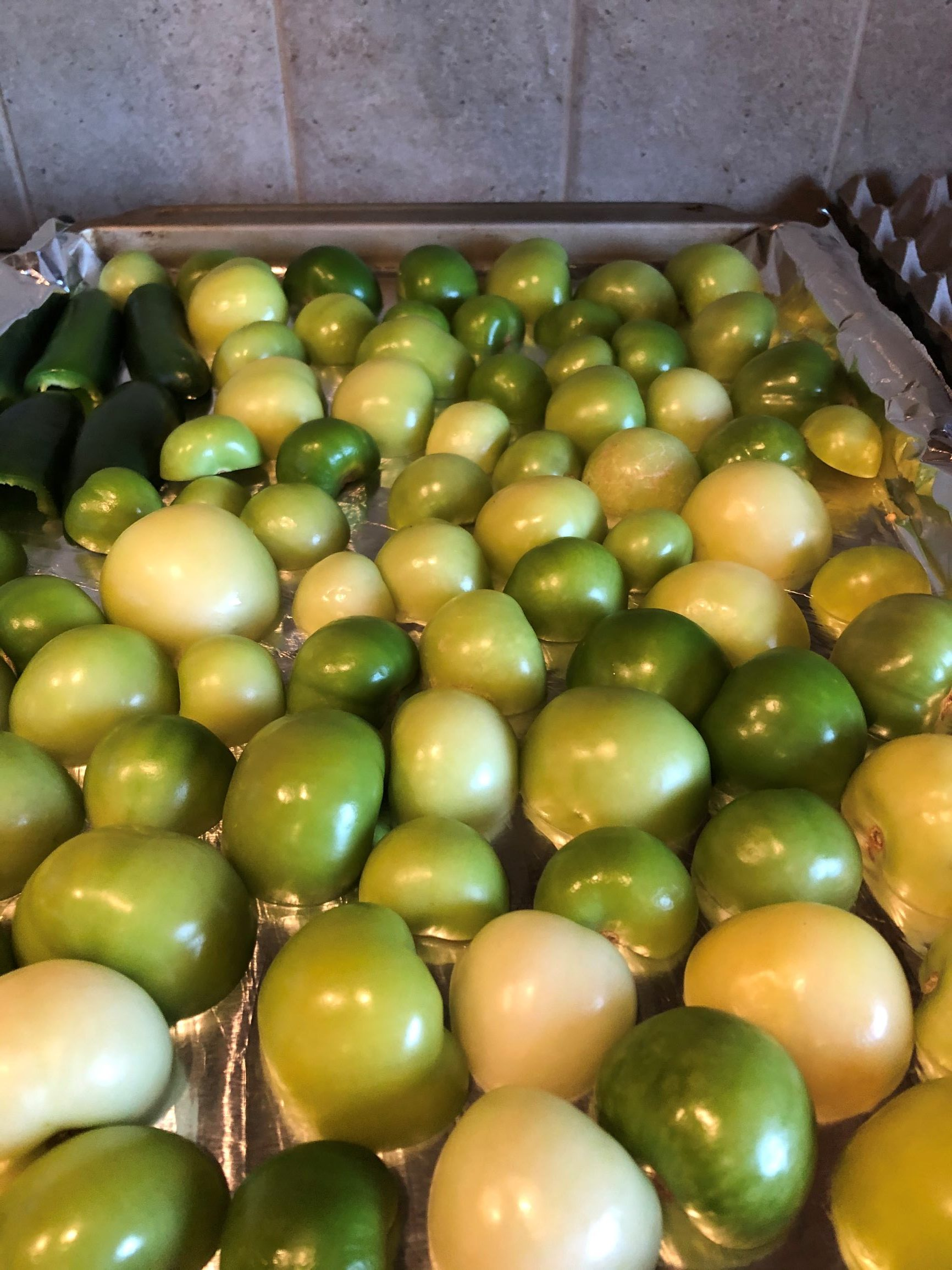Tomatillos ready for roasting on a baking sheet
