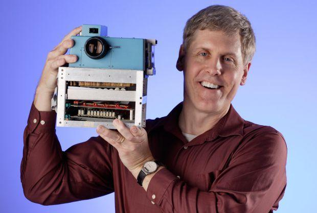 Steve Sasson sosteniendo su invento: la primer cámara digital.
