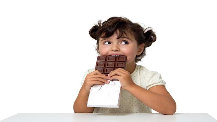 Picture above shows a little girl eating a bar of chocolate