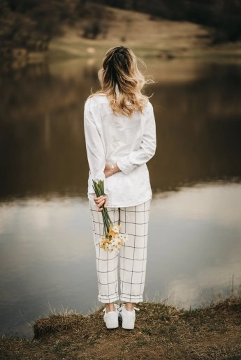 unrecognizable trendy woman with blooming daffodils contemplating river from shore