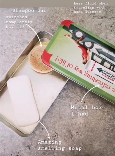 Travel kit containing a metal box, a yellow shampoo bar and a white soap