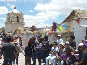 Les villageois et les touristes admirent le spectacle, adossés à l'église