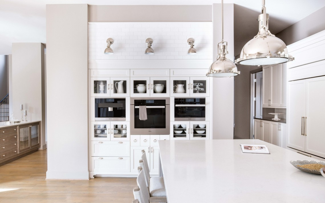White kitchen Miele appliance wall with marble subway tile and polished nickel sconces above