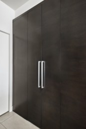 hidden pantry doors in contemporary kitchen with dark oak cabinets