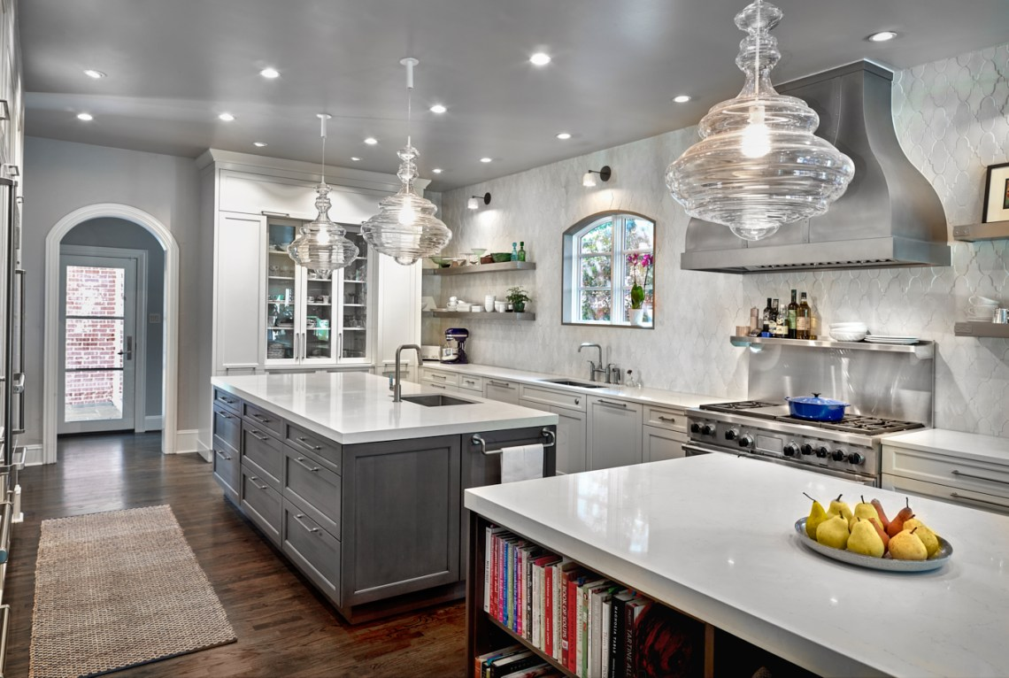 designer kitchen with two islands and open shelving with custom vent hood