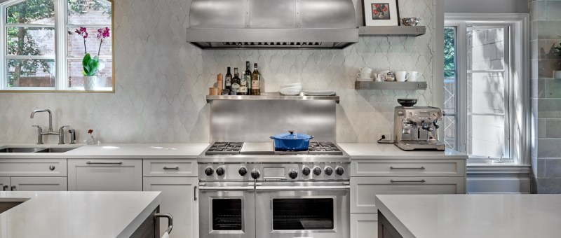 custom stainless vent hood with full height concrete tile backsplash and sconces