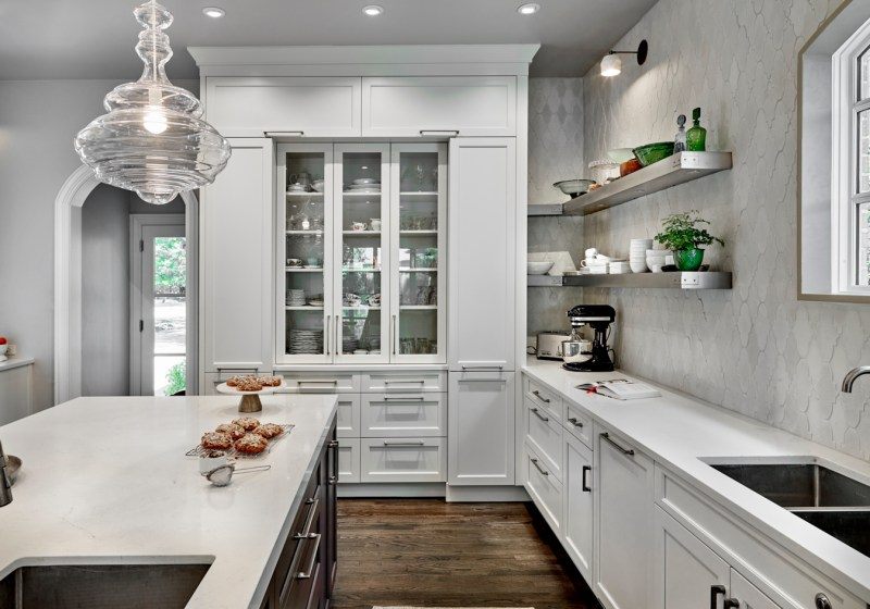 white french-inspired kitchen with glass display cabinetry and baking area