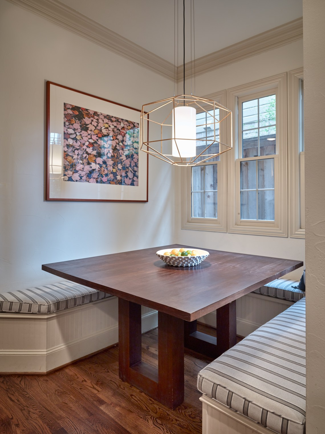 Breakfast nook with striped banquette seating and brass pendant
