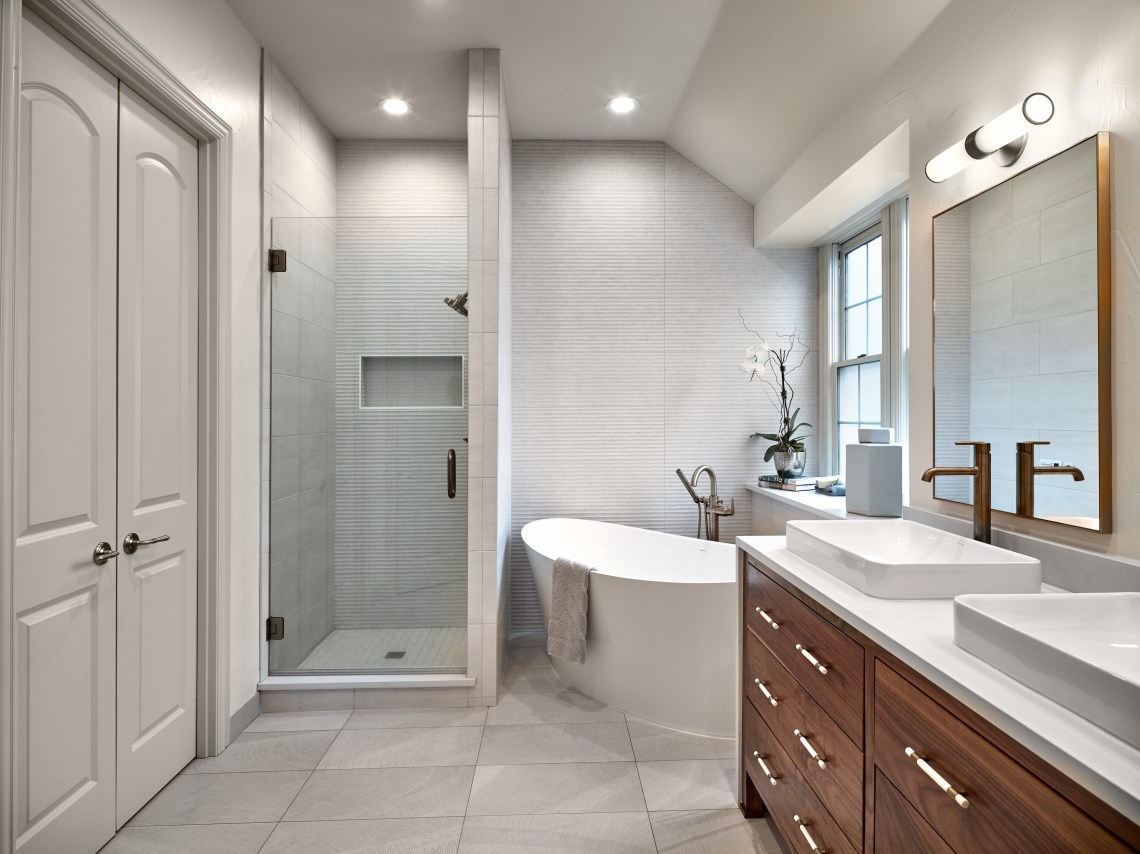 Master bathroom with walnut vanity and vessel sink and freestanding tub and brass fixtures