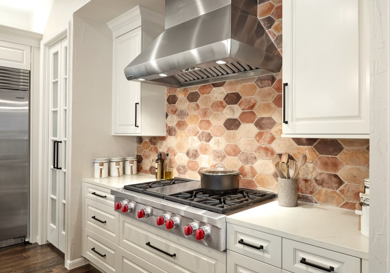 traditional white kitchen with stainless hood and hexagon brick backsplash