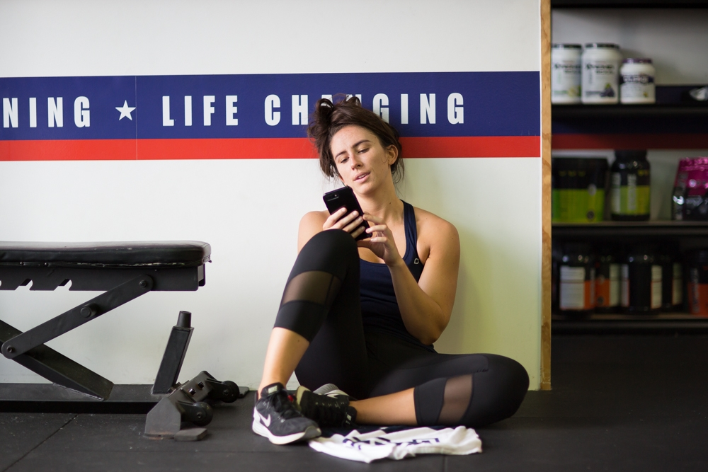 Girl sitting down scrolling through phone after workout