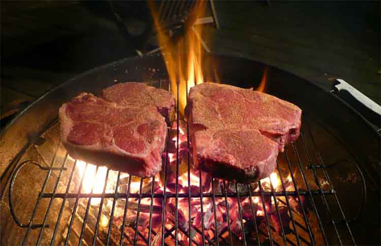 two porterhouse steaks on grill grates