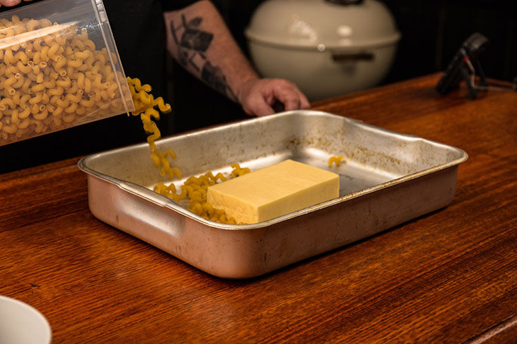 a man adding an uncooked pasta to a metal tray with a block of cheese in it