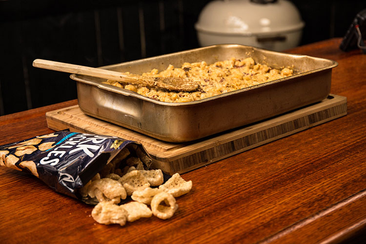a bag of pork rinds and smoked mac and cheese in a metal baking tray