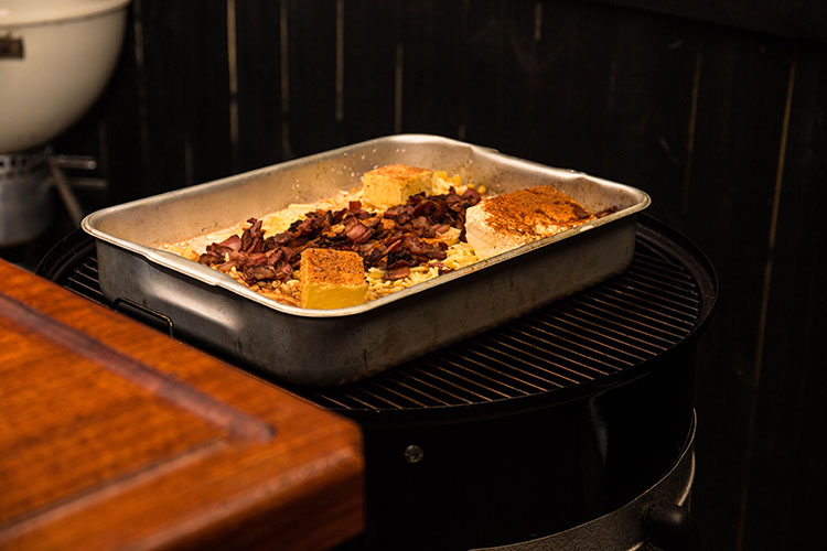 a metal baking tray with uncooked mac and cheese on a weber smokey mountain