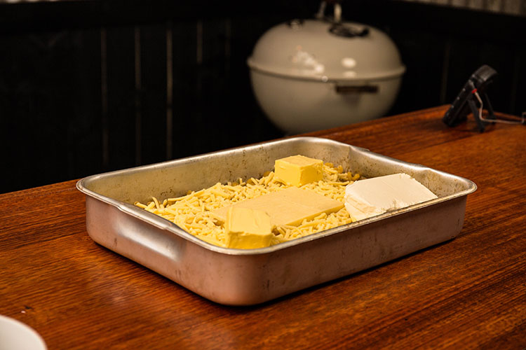 uncooked pasta and cheese in a metal baking tray