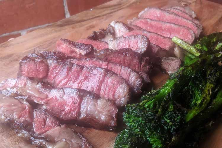 cooked and sliced ribeye steak on a wooden board