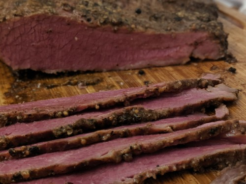 Smoked pastrami sliced on a chopping board