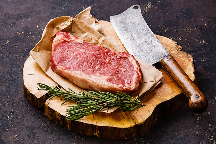Wood butcher block with steak and knife resting