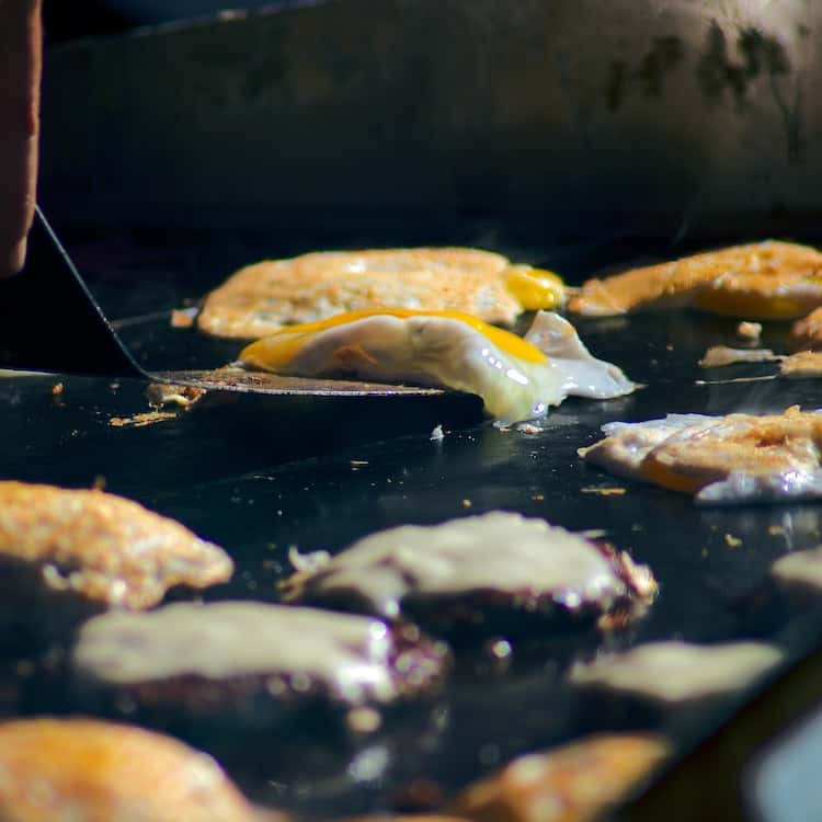 Frying eggs and burger patties with cheese on a griddle