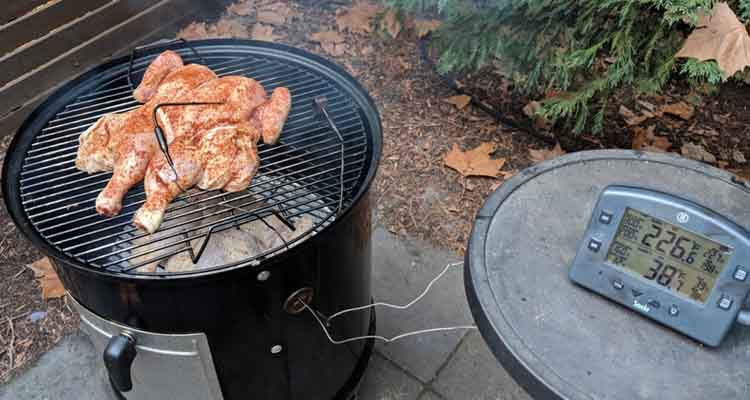 chicken cooking on a charcoal smoker