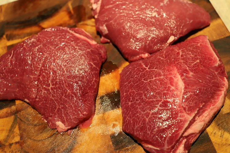 raw beef cheeks on a wooden board