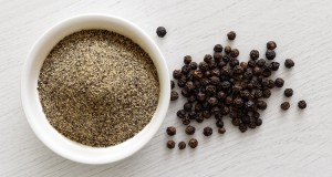ground black pepper in a bowl with peppercorns on a side