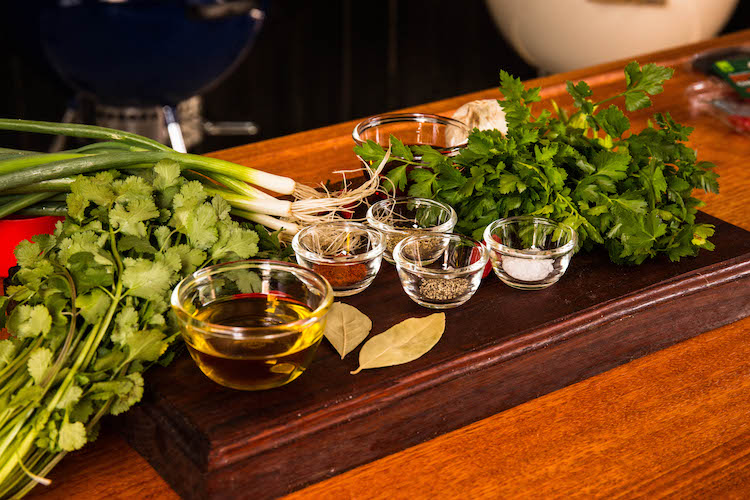 Ingredients for chimichurri sauce on a wooden board