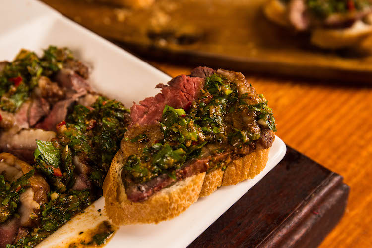 a piece of baguette with a slice of cooked picanha steak and chimichurri sauce