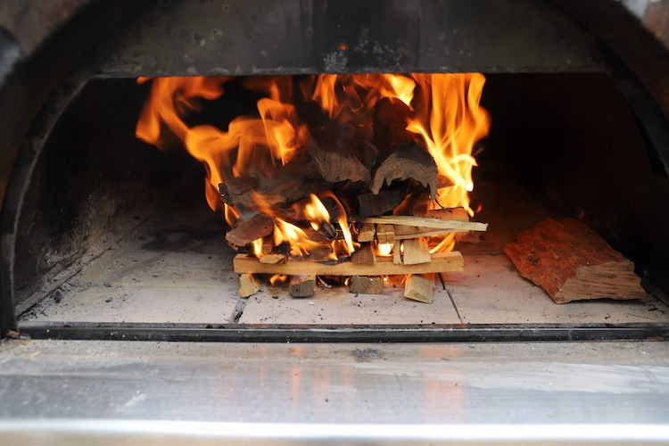 hardwood kindling and firewood burning in a pizza oven
