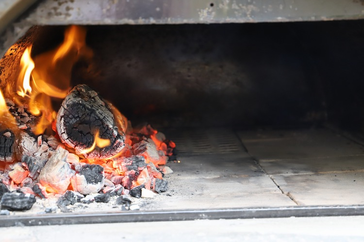 burning coals in a wood fired pizza oven