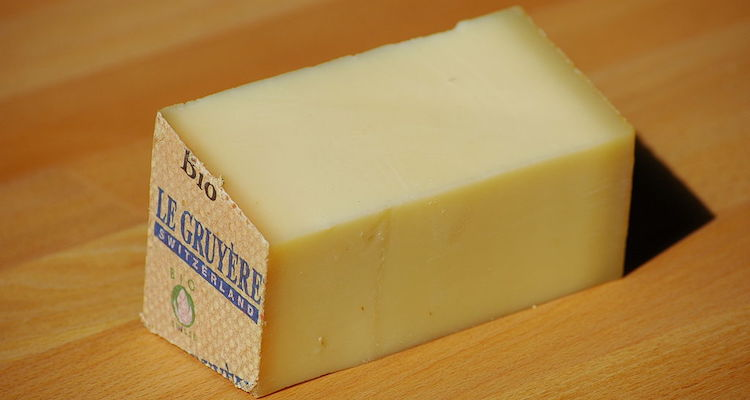 piece of Gruyere cheese on a wooden board