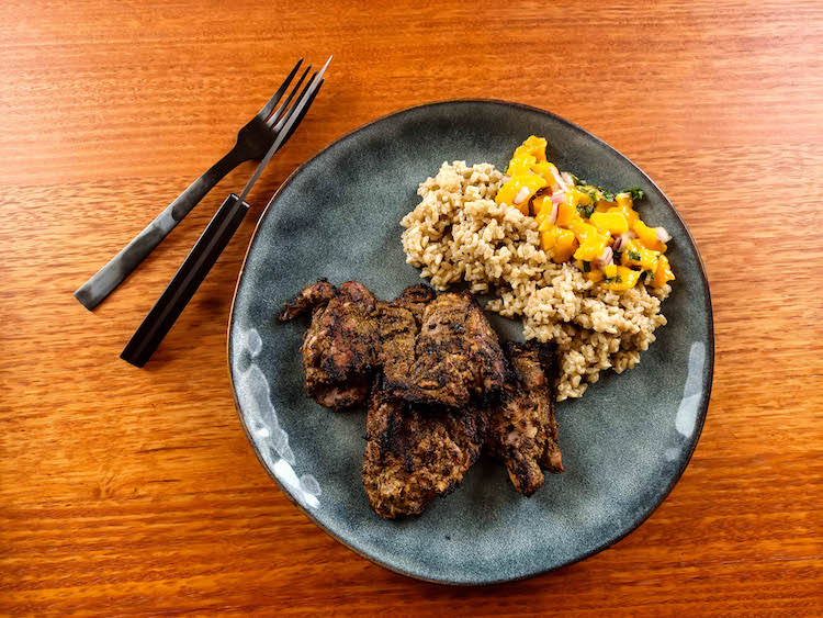grilled jerk chicken thighs with rice and mango salsa on a plate