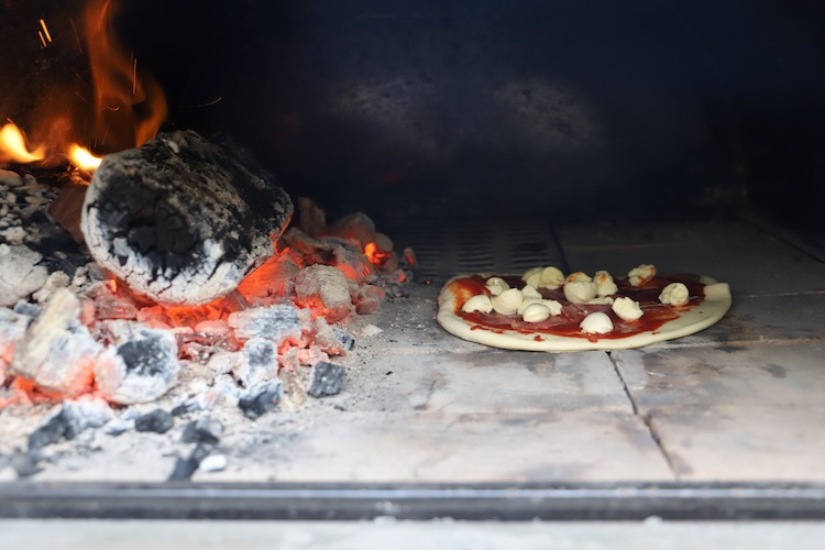 pizza cooking in a wood fired pizza oven