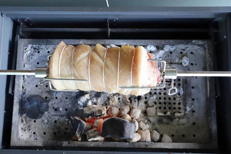uncooked pork belly on a rotisserie over charcoal