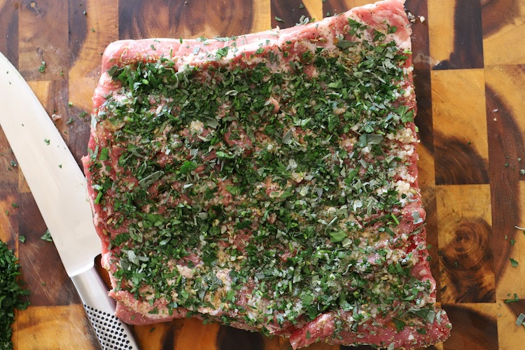 uncooked pork belly rubbed with herbs and spices