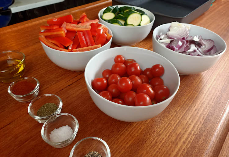 chopped bell peppers, zucchinis, onions and raw tomatoes in bowls