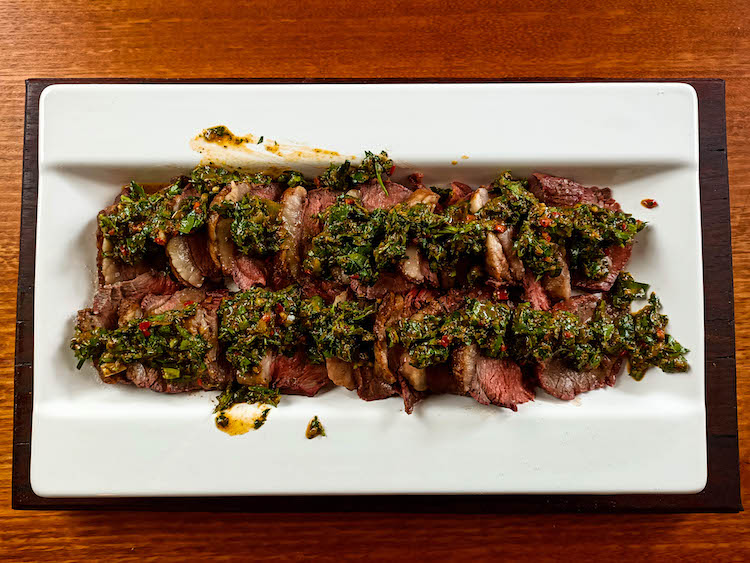 slices of Brazilian picanha steak drizzled with chimichurri on a plate